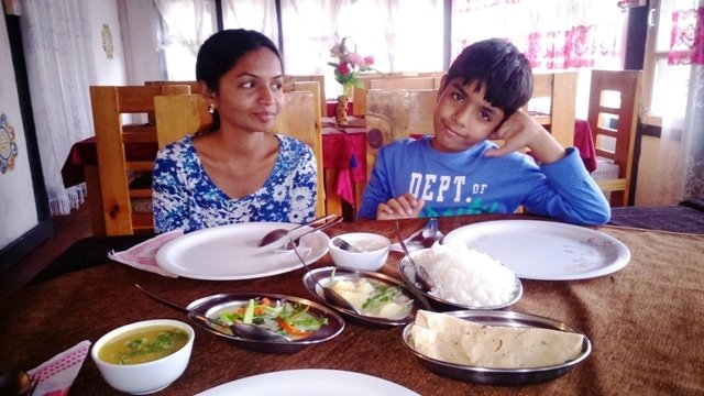 The author and her son enjoying a meal of Ema Datshi with rice and roti